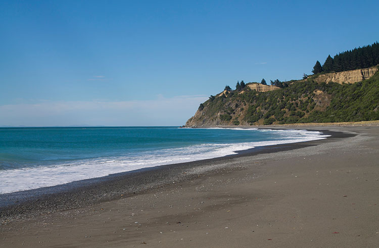 Manuka Bay, a black sand beach in North Canterbury, New Zealand
